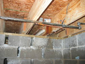 water pipe spraying water into crawlspace