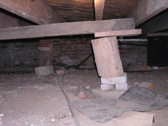 firewood used as support beam under house